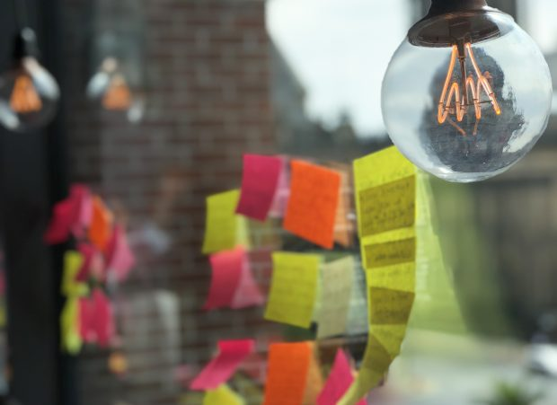 Postit notes on a window with lightbulbs hanging