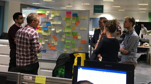 Sheldon and 4 other team members stood around a whiteboard covered in post-it notes. The team are taking part in a regularly held stand-up meeting.