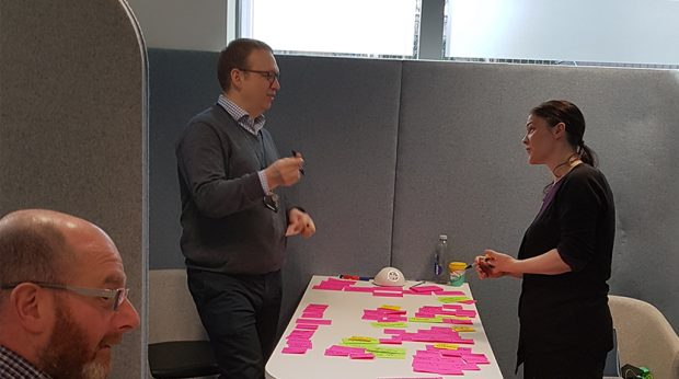 3 members of the pre-discovery team discuss at the kick off workshop, with a table of post-it notes between them.